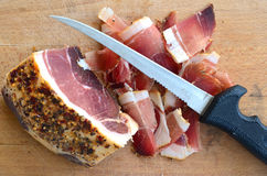 Very spicy prosciutto 5. Homemade spicy proscuitto, smoked and dried in the wind for a long time on wooden chopping board with long, thin knife, view from above Royalty Free Stock Photos
