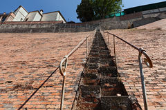 Very steep staircase. Dangerous climb on a high inclined brick wall Stock Images