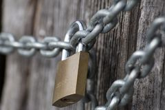 Chain lock on wooden wall. Very strong chain offer safe look together with lock on it Stock Photo