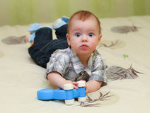 Very surprised baby boy lying on the bed. At home Stock Photography