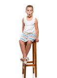 very surprised girl sitting on a chair Stock Image
