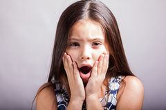Very surprised little girl. Portrait of a Hispanic little girl with her mouth open and hands on her face, acting all surprised on a white background Royalty Free Stock Photo