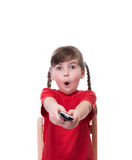 Very surprised little girl wearing red t-short and holding tv re Royalty Free Stock Images