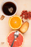 Very sweet breakfast : tea, fresh fruits, madeleine, goji berries Stock Image