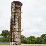 Very tall rusty water tank with two men climbing up its ladder. Royalty Free Stock Image