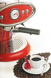 Very tasteful espresso with coffee maker. Very tasteful cup of espresso with beautiful red coffee machine and coffee beans and delicious chocolate Royalty Free Stock Images