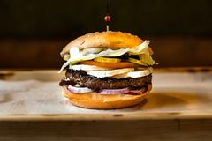 Very tasty burger with a juicy meatball. In cafe royalty free stock image