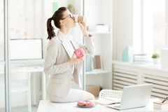 Very tasty. Contemporary businesswoman in suit sitting on desk, drinking tasty coffee and holding appetizing donut with pink glaze and colorful sprinkles Royalty Free Stock Photography