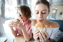 Very tasty. Cute teenage girl looking at hamburger in her hands and looking forwards to eating it Stock Image