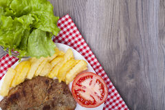 Very tasty lunch on a plate. Pork grilled with fries, tomato and. Fresh lettuce on a wooden background.. With empty space for your text. View from above Royalty Free Stock Images