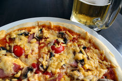 Very tasty pizza with glass of beer royalty free stock photos
