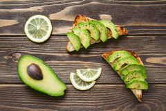 Very tasty toasts with avocado salt and pepper on a wooden table. Royalty Free Stock Photo