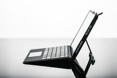 Very thin laptop. A modern, sleek and thin tablet with keyboard or laptop on a shiny surface Royalty Free Stock Image