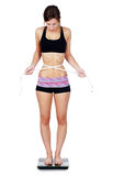 Very thin woman on scale. Very thin or anorexic young woman upset over her weight and waist measurements as she stands on scale Stock Photo