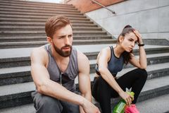 Very tired couple is sitting on steps and having some rest. They have run a lot. Girl is keeping her hand close to the. Head while her boyfriend is just looking royalty free stock photos