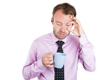 Very tired, almost falling asleep businessman holding a cup of coffee, struggling not to crash and stay awake Royalty Free Stock Images