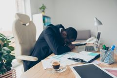 Very tired man with black skin economist, sleep on his hands whi. Le sitting at desk during break time because of routine Royalty Free Stock Photos