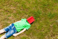 Summer holidays needed. Very tired schoolboy on the grass. Waiting the summer holidays stock photography
