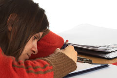 Very Tired Young Caucasian Woman Writing. Very tired young Caucasian woman trying to write and study (Selective Focus, Focus on the right eye and right side of Royalty Free Stock Photo