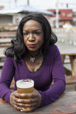 Angry Young African American Woman Drinks Pint of Pale Ale. Very unhappy young African American woman and a pint of pale ale Royalty Free Stock Photos