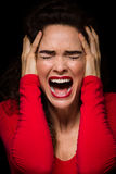 Very upset, emotional and angry woman. A strong dark image of a very upset, angry and emotional woman screaming royalty free stock images