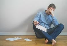 Very upset man. Very upset man sitting at the floor with bills stock photography
