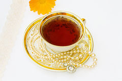 Very vintage breakfast cup of tea with old pearls Royalty Free Stock Photo