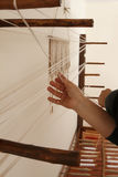 Very vintage loom. A woman work on a old hand-loom royalty free stock images