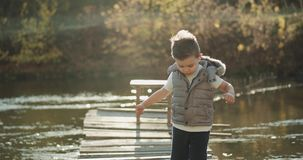 A very wonderful little boy standing in the top of the bridge beside the lake and looking straight to the camera showing stock footage