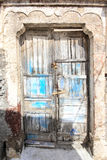 A very worn and battered old blue door Royalty Free Stock Image