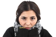 Very wrapped up ill girl with a thermometer Royalty Free Stock Image