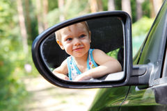 Very young driver in the car mirror Royalty Free Stock Images