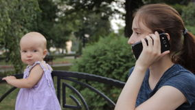 A very young nanny answering the smartphone and talking while the baby is standing next to her holding by the bench back stock footage