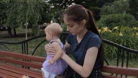 A very young nanny sitting a baby girl next to her and giving her a slice of French bread. The baby girl stands up stock video footage
