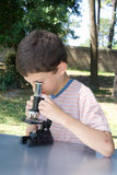 Very young scientist. Schoolboy with microscope, lesson of biology Stock Photos