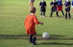 Very  young soccer player. A young soccer player has a major decision to make as he puts the ball into play Stock Photo