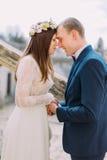 Verzacht de handen van de bruidegomholding en wat betreft door voorhoofden met zijn mooie bruid terwijl allebei zich op antieke s royalty-vrije stock fotografie