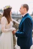Verzacht de handen van de bruidegomholding met zijn mooie bruid terwijl allebei zich op antieke steentreden bevinden Sluit omhoog royalty-vrije stock foto's