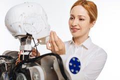 Verzacht gemotiveerde vrouw wat betreft robotsgezicht stock foto