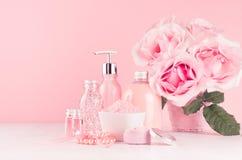 Verzacht meisjesachtige toilettafel met bloemen, schoonheidsmiddelenproducten - nam olie, badzout, room, parfum, katoenen handdoe stock foto