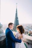 Verzacht mooie bruid en bruidegomholdingshanden met boeket bekijkend elkaar op het oude balkon Royalty-vrije Stock Afbeeldingen