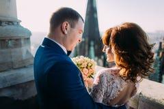 Verzacht mooie bruid en bruidegomholdingshanden met boeket bekijkend elkaar op het oude balkon, close-up royalty-vrije stock fotografie