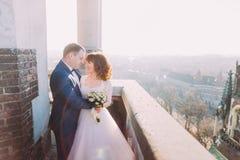 Verzacht mooie bruid en bruidegomholdingshanden van aangezicht tot aangezicht omhelzend op het oude balkon, achtergrondcityscape stock fotografie