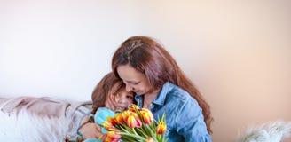 Verzacht omhelzingenmoeders en dochters, gelukwensen op de vakantie en bloemen Het concept van de de groetkaart van de moeder` s  royalty-vrije stock afbeelding