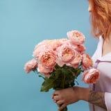 Verzacht roze rozen in de handen van een meisje met een tatoegering op een blauwe achtergrond met exemplaarruimte voor tekst Verj stock foto