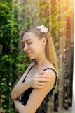Verzacht zacht portret van meisje dat in straat in douche met bloem in haar hoofd wordt gebaad stock foto's
