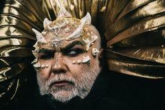 Verzaubertes cyclope mit den Dornen und den Warzen auf Gesicht Blinder Zauberer über goldenem metallischem Hintergrund Mythisches Stockbild