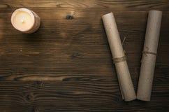Verzeichnen Sie Papierseite und eine Kerze auf hölzernem Schreibtischtabellenhintergrund mit Kopienraum in einer Liste Scheren un Lizenzfreies Stockbild