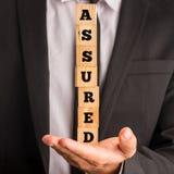 Verzekerde de Spelling van zakenmanholding letter blocks stock foto