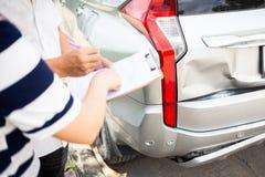 Verzekeringsagent die op klembord schrijven terwijl achterin het onderzoeken van de auto stock fotografie